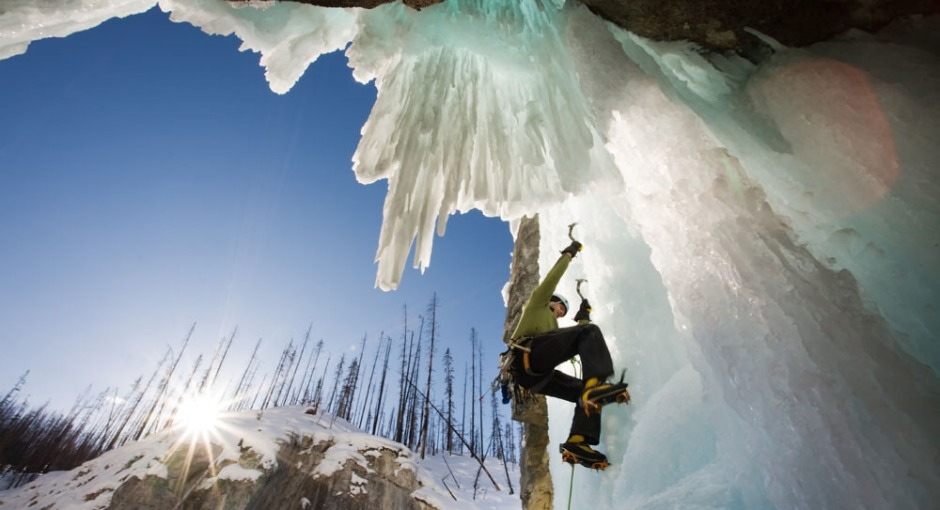 Young man climbing frozen waterfall in the Rocky Mountains of Canada